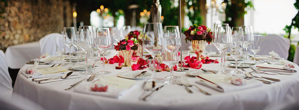 Image contains a table with silverware, plates, wine glasses, and flowers