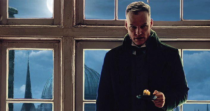 Image of man with short hair standing in the shadows with prop of large windows behind him. He's wearing a coat from the era of Dickens classis A Christmas Carol; holidng a candle in a holder