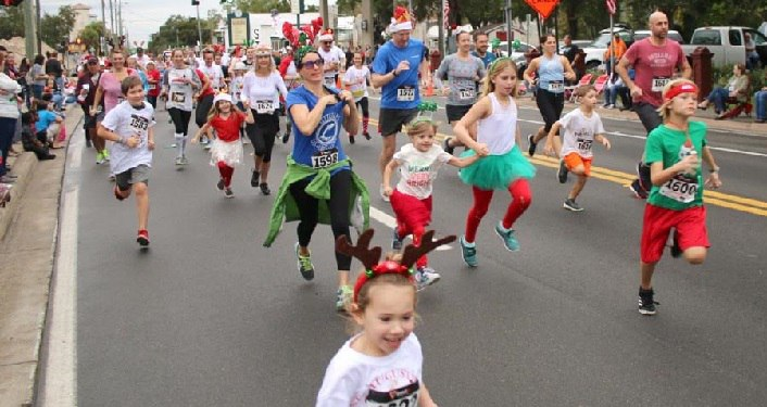 image of runners, young and old, from young boys and girls to adults running in annual Reindeer Run. Some wearing reindeer antlers, some red and green for Chistmas season