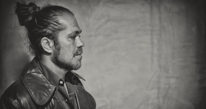 press photo of Citizen Cope; image in black and white. Side View of man in mid 30s, with hair pulled back and braided on side. He's got a mustache and sideburns; he's wearing a jean jacket