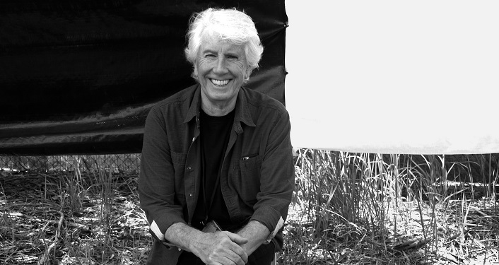 press photo in black and white of Grammy-award winner Graham Nash, man with white hair sitting on a chair; wearing denim jacket over black top