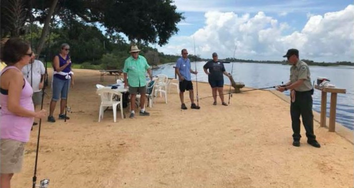 image of 1 woman, 3 men holding fishing poles, standing by water listening to park ranger during Intermediate Saltwater Fishing