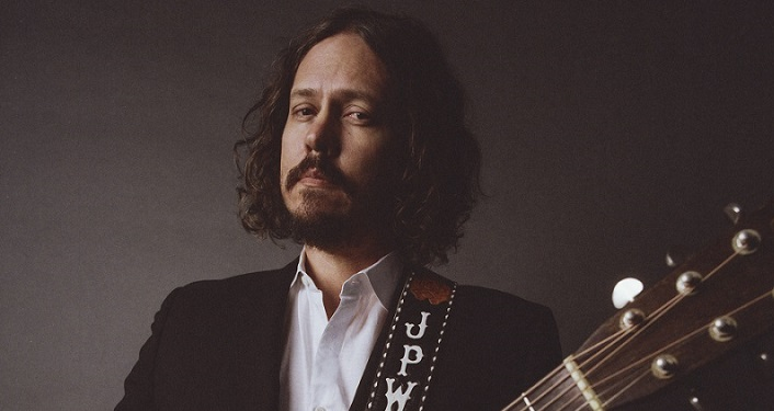 image from shoulders up of Grammy Award-Winning Americana singer/songwriter John Paul White; whtie man with brown hair, mustache and trimmed beard holding guitar, wearing white shirt with sport jacket