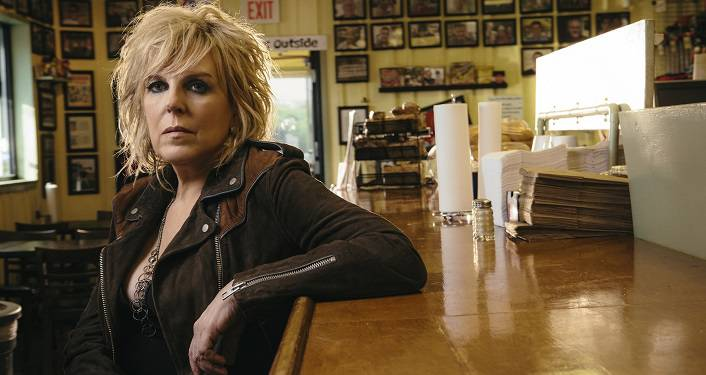 press photo of Award-winning, Americana artist Lucinda Williams. woman with blonde hair sitting with arm resting on bartop. In her late 40s-ish, wearing brown , long-sleeved top