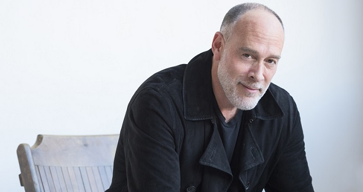 image of middle-aged man, sitting in chair. He's wearing black jacket over navy t-shirt. He has receding hairline, salt & pepper colored hair, white close shaved beard. Grammy Award-Winning, soulful singer-songwriter Marc Cohn