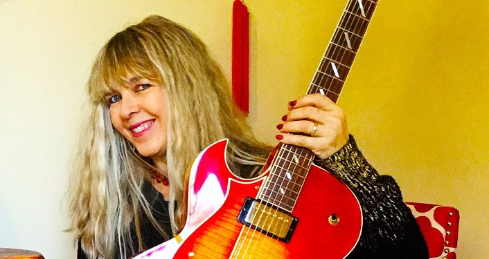 image of Local musician Marianne Lerbs. long hair, blondish colored woman smiling, holding electric guitar that is mostly red with a bit of white.