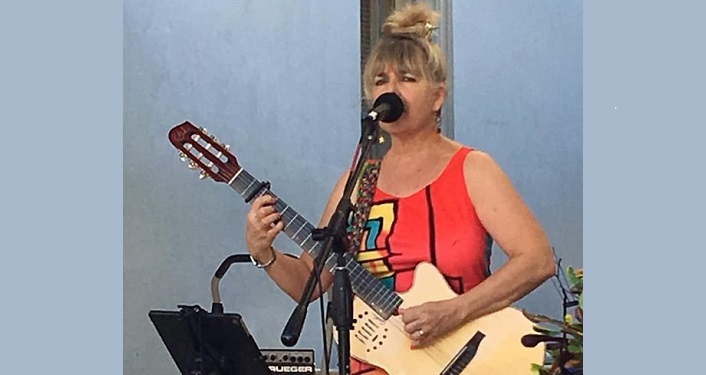 image of Marianne Lerbs; standing at microphone, playing guitar and signing into it. Wearing red sleeveless dress, sandy brown hair piled in bun ontop of her head