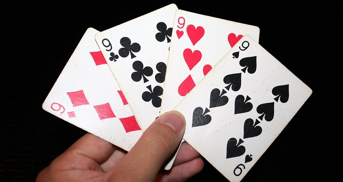 image of hand holding all four 9's in deck onf playing cards during Card Club Playing Event