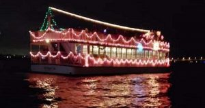 image taken at night of Scenic Cruise decorated to participate in Regatta of Lights; covered tour boat approximately 150ft long decorated with white lights and a Santa