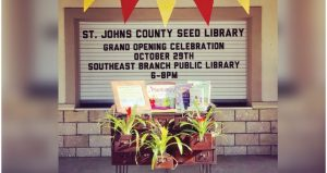 image of sign with text; St. Johns County Seed Library Grand Opening October 29th. display beneath the sign with three differnt blooming plants