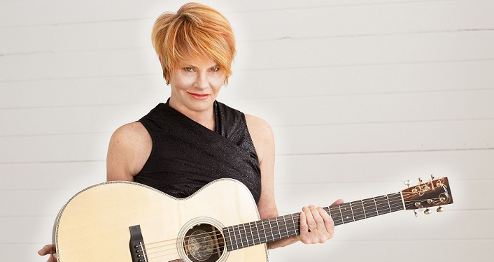 press photo of Grammy Award-Winning artist Shawn Colvin; woman with short red hair, wearing short-sleeved black top and holding a guitar
