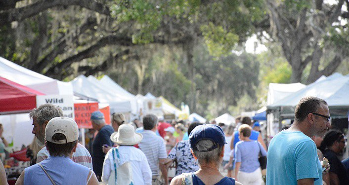 image of lots of people walking, browsing at various vendor tents set up outside at St. Augustine Amphitheatre Farmers Market