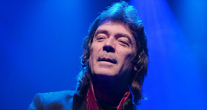 head shot of progressive rock guitarist Steve Hackett; man with shoulder length brown hair approximately mid-60s wearing dark blue jacket, red scarve around his shoulders