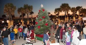 image at St. Augustine Beach Pier Park of Christmas tree with Santa sitting in a chair and lots of people mingling around during Surf Illumination