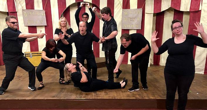 image of 7 people, men & women all dressed in black, on stage performing various improv acts