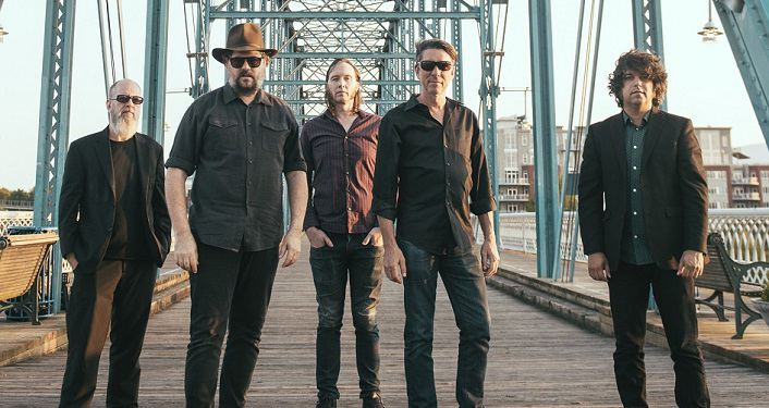 press photo, Hard-touring, southern alt-country rockers Drive-By Truckers; five men standing on a bridge looking towards camera; one wearing a hat, all wearing darker clothes, three wearing sunglasses
