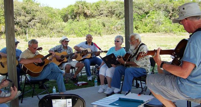 image of men and women sitting under covered pavilion; some playing guitars, some banjo, some mandolin at Gamble Jam