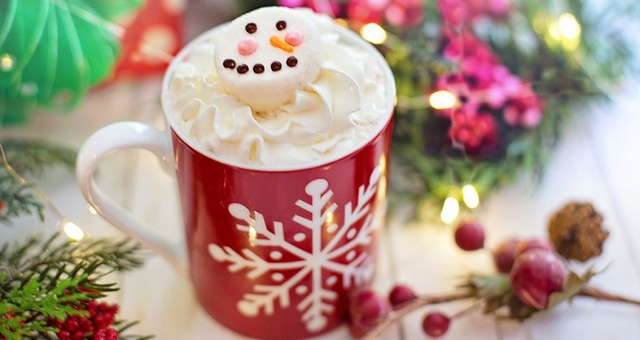 Image of red mug with snowflake on it filled with hot chocolate and whipped cream,with marshmallow decorated like snowman. sprigs of greenery and holly