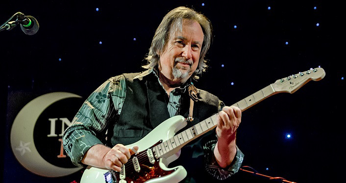 press photo of Jim Messina in Concert, half of the soft rock duo Loggins and Messina. Man with shoulder length hair, mustache and neatly trimmed beard standing playing white bass guitar. He's wearing turguiose plaid shirt with brown vest