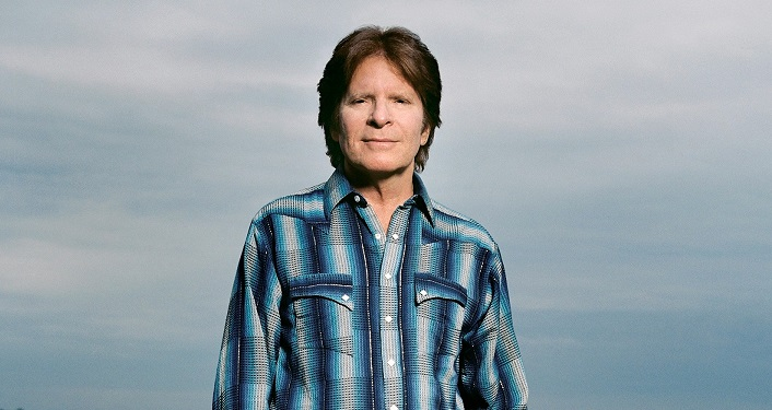press photo of Rock Icon John Forgerty; man in early 70's with dark brown hair, wearing blue plaid shirt