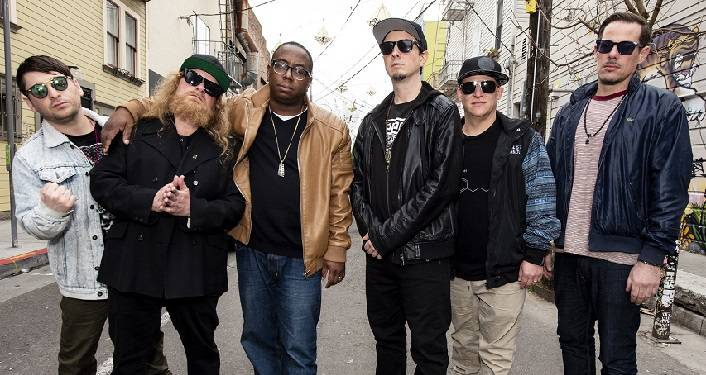 press photo of New York based funk band LETTUCE; 6 guys standing on a street, all wearing sunglasses.