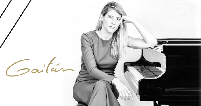 black & white image of woman with long hair, wearing a gown, sitting on piano bench with left arm propped on piano; Internationally acclaimed pianist, Maria Dolores Gaitán