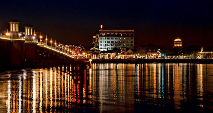 image at night from the water of Bridge of Lions and bayfront in St. Augustine lit up with millions of tiny, white lights during Nights of Lights