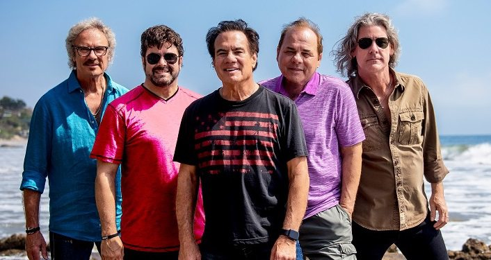 Pablo Cruise Press Photo; 5 middle-aged men standing with ocean in background. One wearing blue shirt, one wearing pink shirt, one purple shirt, one tan shirt, and one dark grey t-shirt with pink lettering
