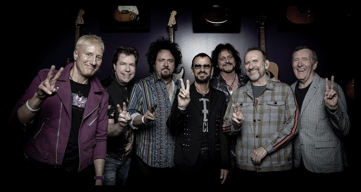 press photo of Ringo Starr and His All Starr Band; six middle-aged men standing looking into camera. Former Beatle, Ringo is making peace sign with right hand.