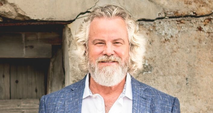 press photo of Legendary Americana pioneer Robert Earl Keen; men with full head of white-grey hair and beard, wearing denim blue colored jacket, light blue shirt