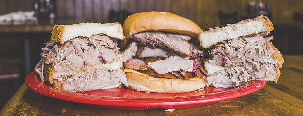 Image contains three pulled pork sandwiches on a plate.