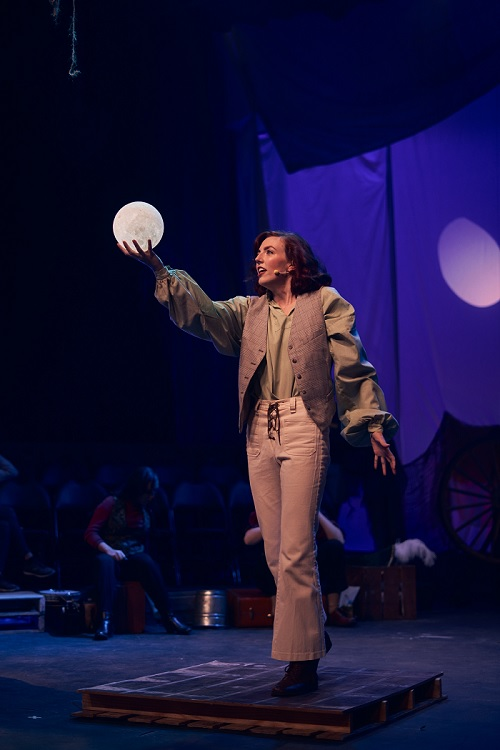 Image contains a woman standing straight holding a fake moon in her hand.