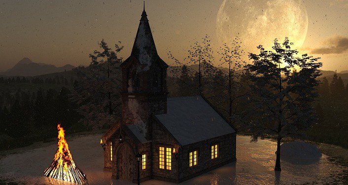 image of church at dusk with sun setting in background, lit Christmas tree in front of church