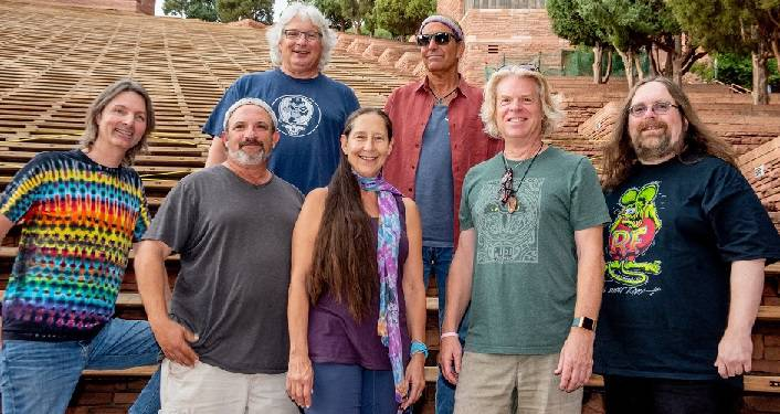Dark Star Orchestra Press Photo; 7 middle aged people, 6 men & 1 woman. All looking at camera & laughing, wearing jeans & t-shirts.