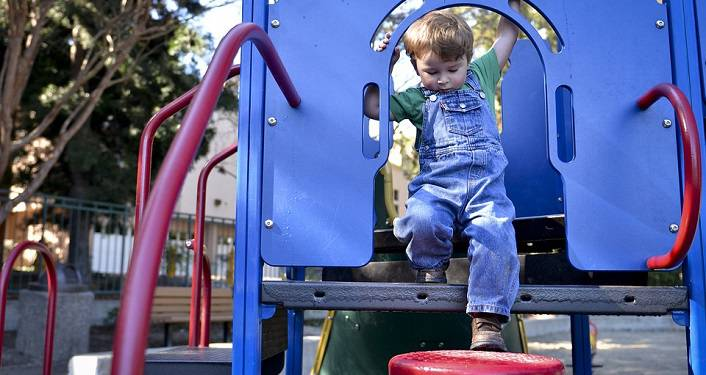 image of young boy dressed in blue overalls playing on the playing gym set during Kids Holiday Break Camp