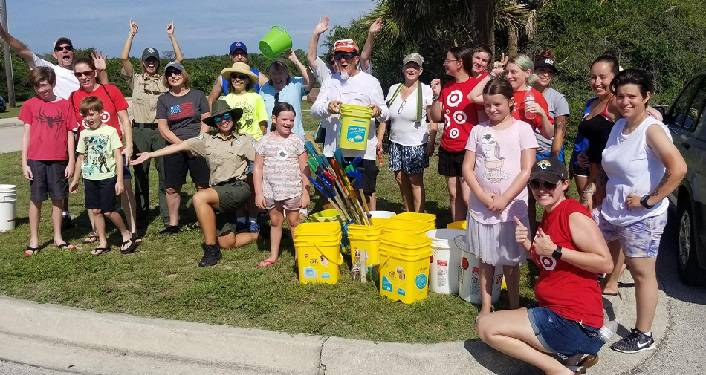 image of men and women and children standing with buckets after Anastasia State Park Coastal Cleanup