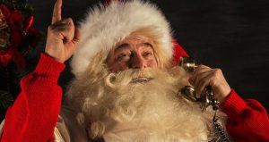 image of Santa Claus smiling, talking on the phone