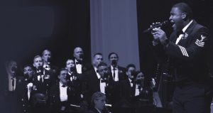 image of US Navy Band in Concert; one man in uniform standing signing into microphone, several others sitting in orchestra in uniform with their insturments
