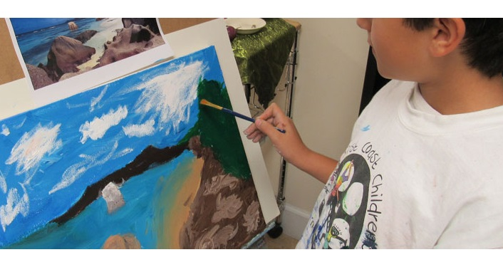 image of young boy from the side painting a picture on as easel