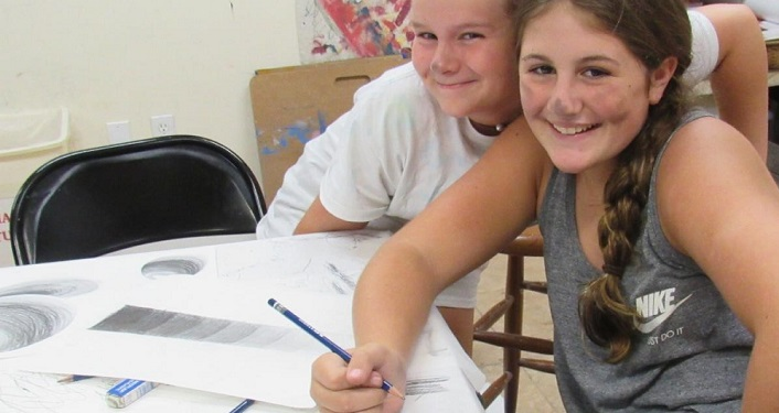 image of two girls smiling; one holding a colored pencil above an image on paper she was drawing