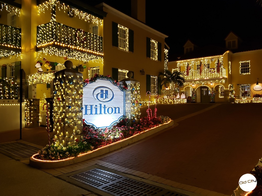 Image contains the entrance way of a hotel decorated in many holiday lights and ornaments.