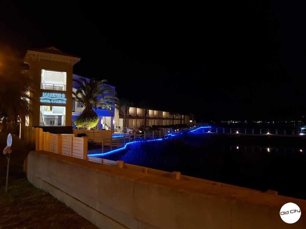 Image contains a marina next to a hotel that is decorated in lights.