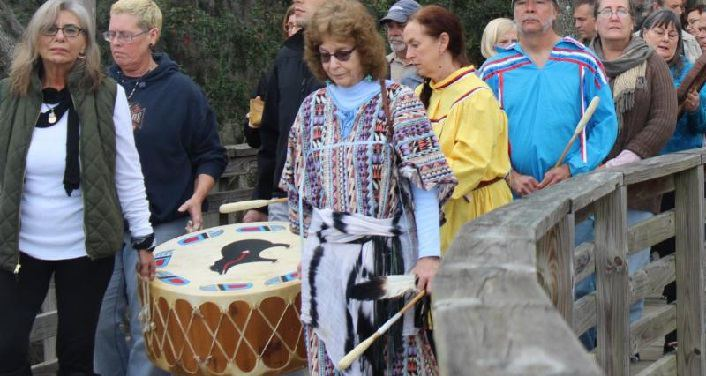 two women carrying drum, followed by several man and women - Annual River Blessing