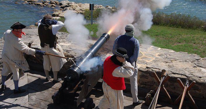 image of reenactors dressed like British Navy firing cannon at Fort Matanzas