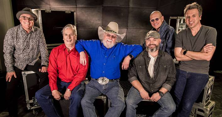 The Charlie Daniels Band Press Photo: 6 men ranging from middle to older age, Charlie Daniels in the middle wearing bright blue shirt, cowboy hat