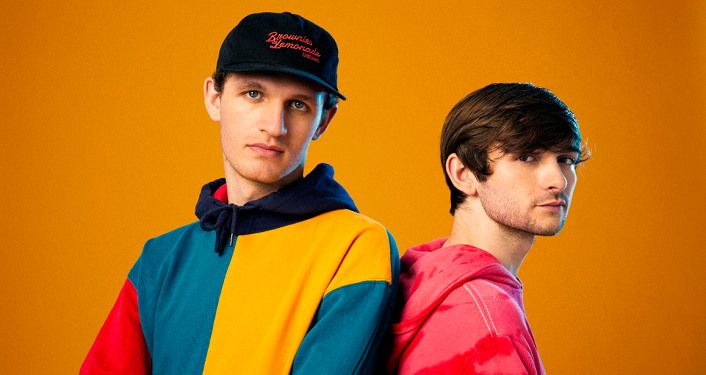 Press photo of DJ and production duo, Louis the Child. 2 younger men standing next to each other; one of left wearing baseball cap, turquiose & yellow hoodie, one on right with red hoodie.