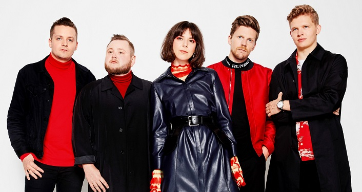 Of Monsters and Men Press Photo; 4 men, 1 woman - 3 men dressed in red shirts, black jackets, 1 in black shirt, red jacket. woman standing in middle had on black leather coat, wearing red scarf and mittens.