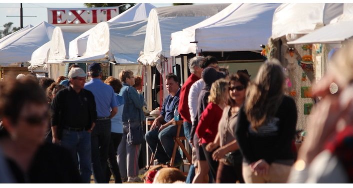Image of people (men & women, young & old, children also) standing at several booths with artists/artwork at Old Town Art Show