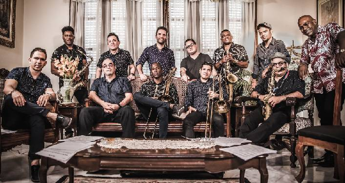 press photo of Cuban mambo band Orquesta Akokán. 12 men ranging in age; 5 sitting, 7 standing behind them; 2 holding trumpets, 2 holding saxaphones.