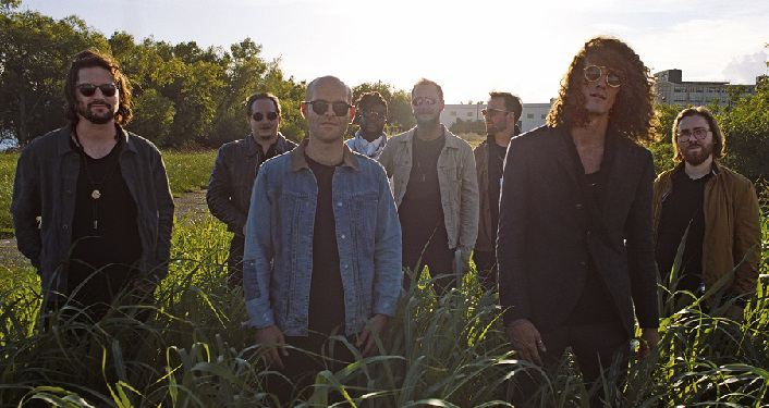 The Revivalists Press Photo; 8 men dressed in casual clothes standing in a field with the sun behind them